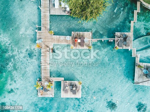 Aerial shot of woman relaxing in a water bungalow