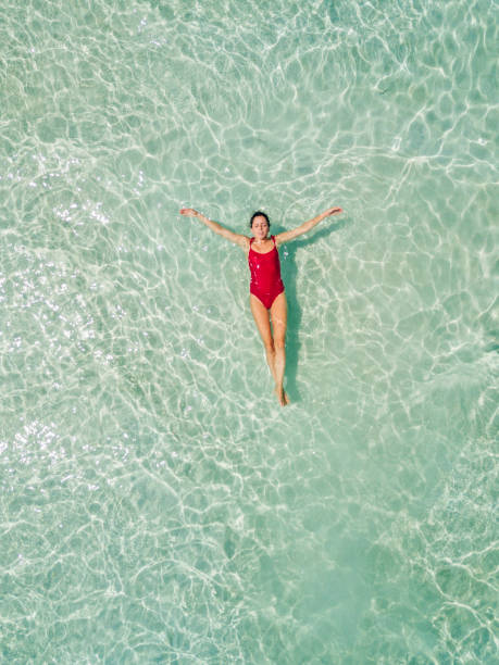 Aerial shot of woman relaxing in the beach Aerial shot of woman relaxing in the beach floating on water stock pictures, royalty-free photos & images