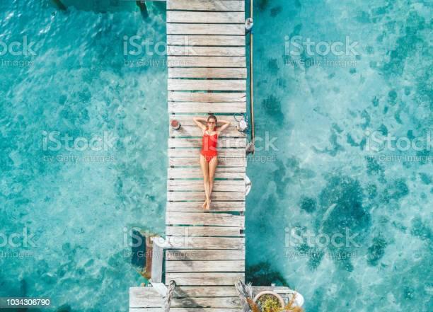 Aerial shot of womann relaxing in a water bungalow picture id1034306790?b=1&k=6&m=1034306790&s=612x612&h=pieppjxettqesmnhitbfyaz 2ekdnpjvlbzj6 n5i4a=