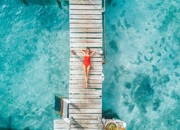 aerial shot de womann relaxante em um bangalô de água - laguna - fotografias e filmes do acervo