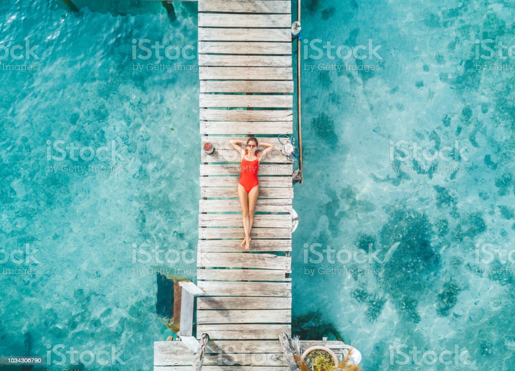 Aerial shot of womann relaxing in a water bungalow stock photo