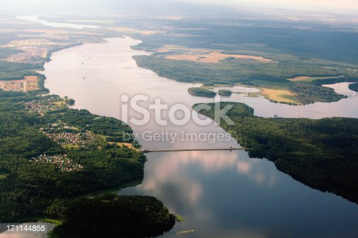A scenic aerial shot of a flowing river and the surrounding forest in Russia. The bright and clear sky can be seen reflected in the water that is surrounded by lush greenery and a few fields. It is a sunny day and the sun is shining on the water that is everywhere.