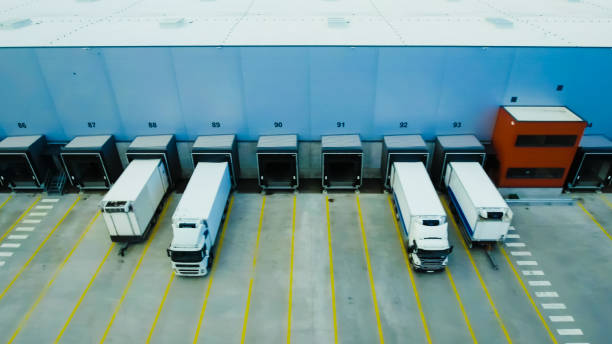 aerial side shot of industrial warehouse loading dock where many truck with semi trailers load/ unload merchandise. - lorries unloading stock photos and pictures