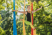 Aerial silk artist performing movements on ropes hanging from trees on a sunny day in Tivoli park, Ljubljana.