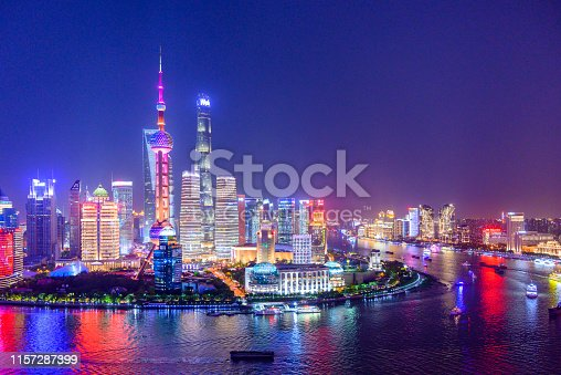 Aerial skyline view of Shanghai at dusk showing the financial district of Pudong and its tall skyscrapers.