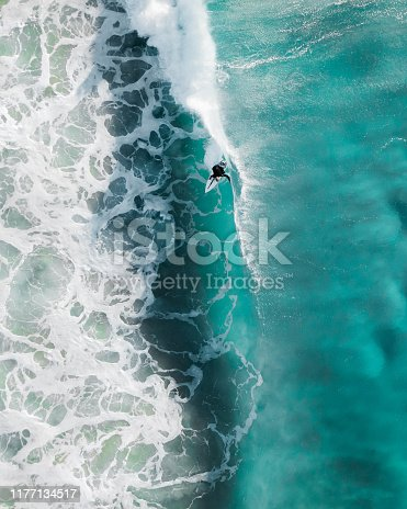 Aerial sport action shot of a surfer at sunrise riding a wave in a blue ocean in Sydney, Australia Bondi Beach