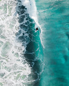 Aerial sport action shot of a surfer at sunrise riding a wave in a blue ocean in Sydney, Australia Bondi Beach