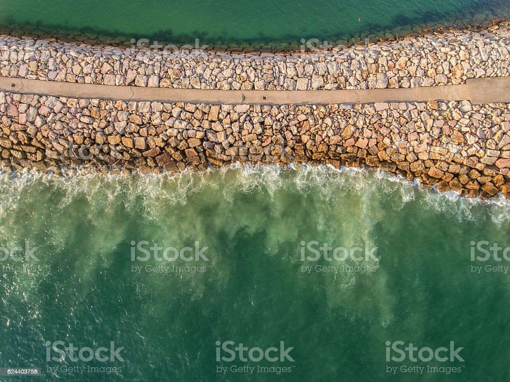 Aerial. Stone Industrial breakwater into the sea. Filmed from the stock photo