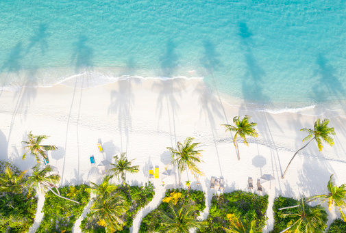 Aerial of the beautiful secluded white sand beach on a small maldives island. Sun setting casting shadows in to the turquoise ocean. Converted from RAW.