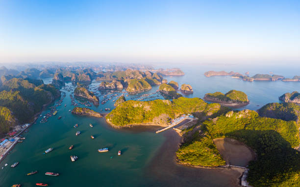 Aerial sunset view of Lan Ha bay and Cat Ba island, Vietnam, unique limestone rock islands and karst formation peaks in the sea, floating fishermen villages and fish farms from above. Clear blue sky. stock photo