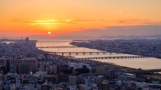 Aerial sunset view of Osaka skyline with the river, round sun, and golden sky as seen from Umeda Sky Building.