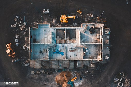Drone footage of the inside of a house under construction surrounded by building equipment taken at sunrise in spring 2019