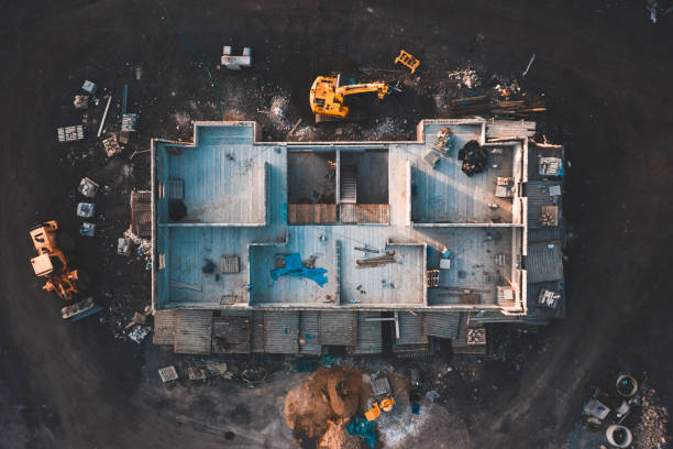 Aerial top down shot of a house frame on a construction site surrounded by mud Drone footage of the inside of a house under construction surrounded by building equipment taken at sunrise in spring 2019 construction industry stock pictures, royalty-free photos & images