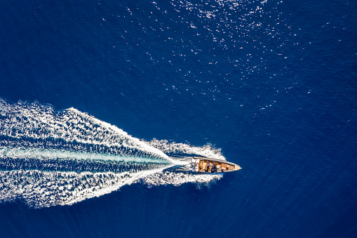 Aerial top down view of a motorboat traveling over blue sea