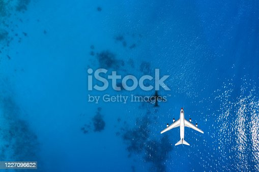 1058205304 istock photo Aerial top down view of an airplane flying over blue sea 1227096622