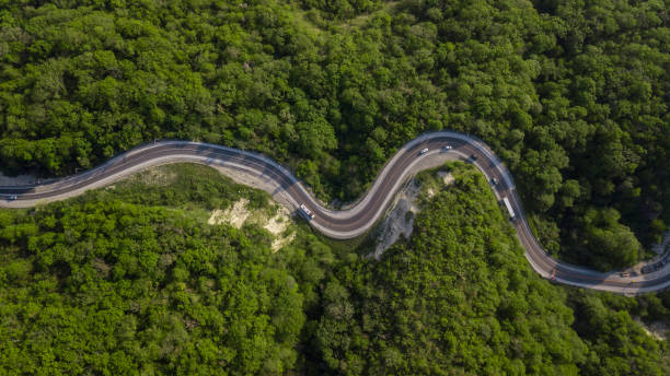 Aerial top down view: of cars driving on zig zag winding mountain road Curvy switchback highway with hairpin turns snaking through the woods southeast england stock pictures, royalty-free photos & images