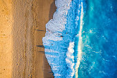 Aerial top down view to a beautiful beach with big, turquoise colored waves and warm sunlight during sunset time
