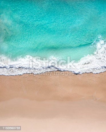 Aerial top shot of a beach with nice sand, blue turquoise water and tropical vibe of a superb tropical destination