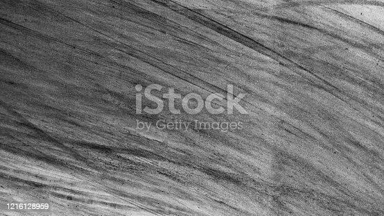 1095367134 istock photo Aerial top view abstract texture and background asphalt road with car tire track skid mark on race track, Abstract texture of car drift tire track skid mark black and white, Automobile concept. 1216128959