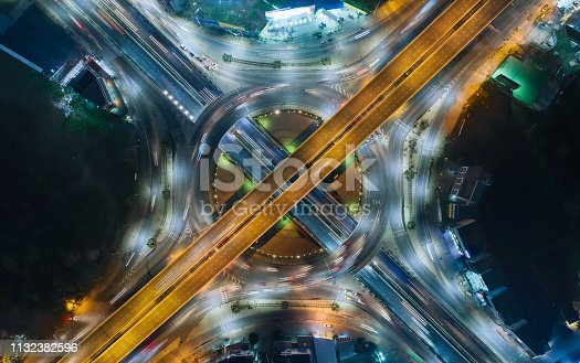 Aerial top view highway road intersection roundabout or circle at night for transportation, distribution or traffic background.