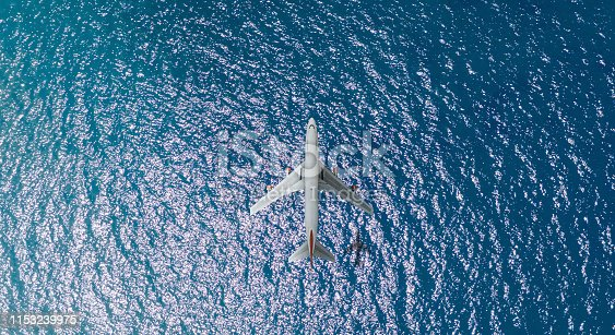 1058205304 istock photo Aerial top view of Airplane flies over a sea 1153239975