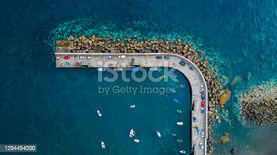 Aerial top view of antique harbor with wooden boats in Paul do Mar, Madeira island, Portugal