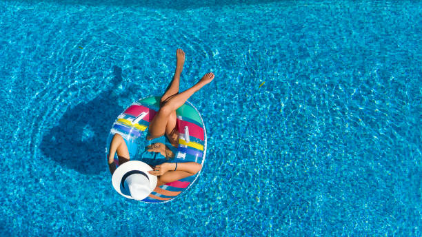 Aerial top view of beautiful girl in swimming pool from above, relax swim on inflatable ring donut and has fun in water on family vacation stock photo