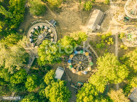 aerial top view of city park caorusel with happy children on summer holidays