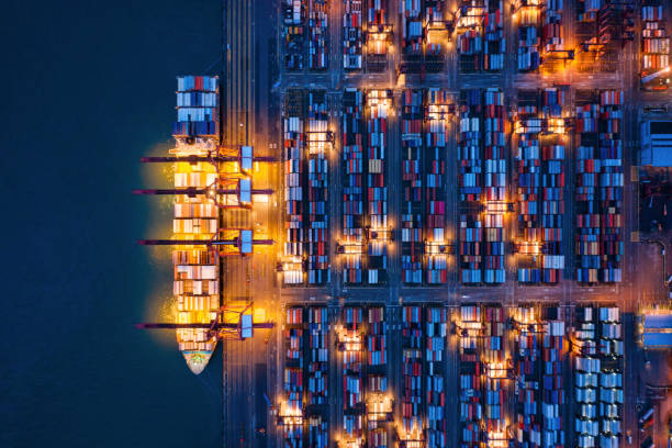 Aerial top view of container cargo ship in the export and import business and logistics international goods in urban city. Shipping to the harbor by crane in Victoria Harbour, Hong Kong City at night. stock photo