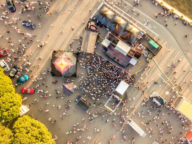 aerial top view of crowd of people standing near the stage on concert on summer day - film festival stock photos and pictures