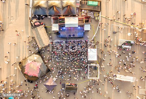 aerial top view of crowd of people standing near the stage on a concert on summer day