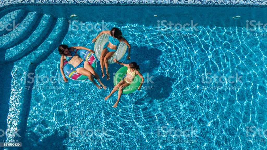 Aerial top view of family in swimming pool from above, mother and kids swim and have fun in water on family vacation stock photo