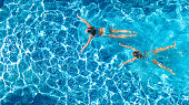 Aerial top view of girls in swimming pool water from above, active children swim, kids have fun on tropical family vacation, holiday resort concept