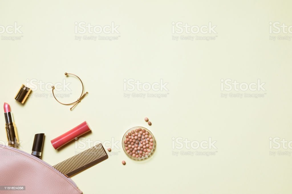 Aerial top view of makeup bag with cosmetic products spilling out on...