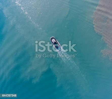 istock Aerial top view of motion tugboat at azure water with a spot of oil 644267348