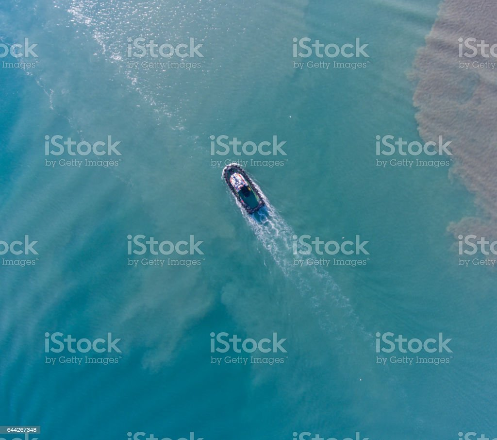 Aerial top view of motion tugboat at azure water with a spot of oil stock photo