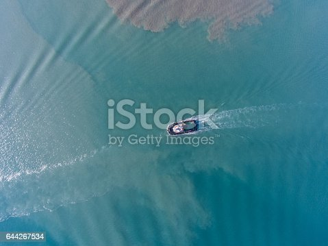 istock Aerial top view of motion tugboat at azure water with a spot of oil 644267534