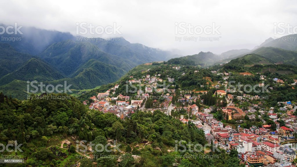 Aerial top view Of Sapa Town cityscape with heavy mist in the valley, Vietnam. Landscape of city with Beautiful natural mountain stock photo