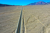 Aerial top view of the mountains and endless highway road in Death Valley national park, USA country
