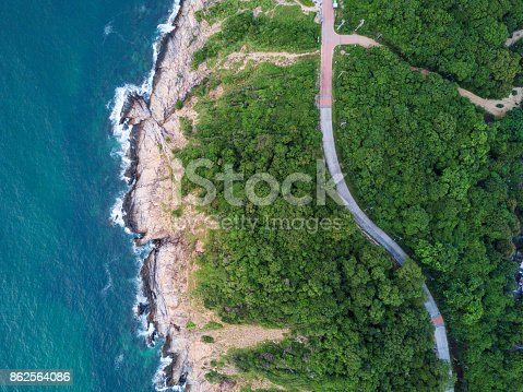 istock Aerial Top View of the road through Green forest on the mountain on Tropical Island with ocean side. The scenic aerial landscape of nature on a green hill with a road through the wood. 862564086