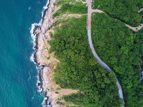 Aerial Top View of the road through Green forest on the mountain on Tropical Island with ocean side. The scenic aerial landscape of nature on a green hill with a road through the wood.