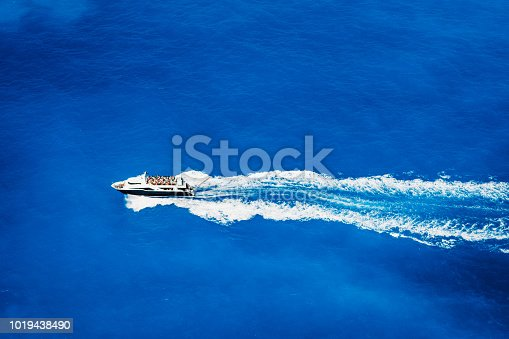 1066331604 istock photo Aerial top view of tourist speed boat sailing in the deep blue sea 1019438490