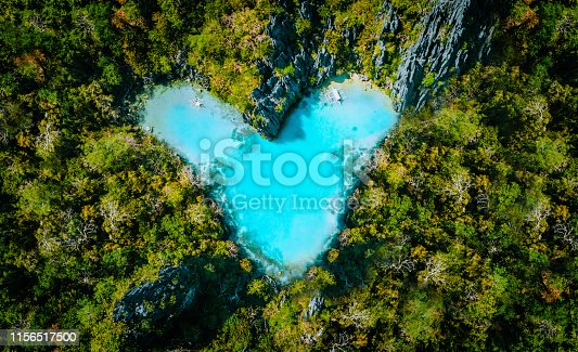 Aerial top view of turquoise lagoon shaped heart inside of tropical island. Love travel summer vacation concept.