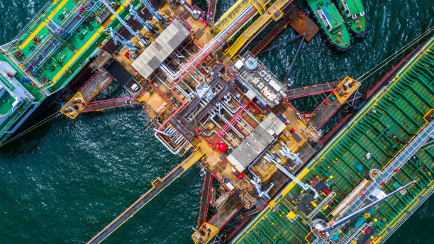 Aerial top view of two fuel tanker ship at the port, Oil terminal is industrial facility for storage of oil and gas petrochemical products ready for transport to further storage facilities. stock photo