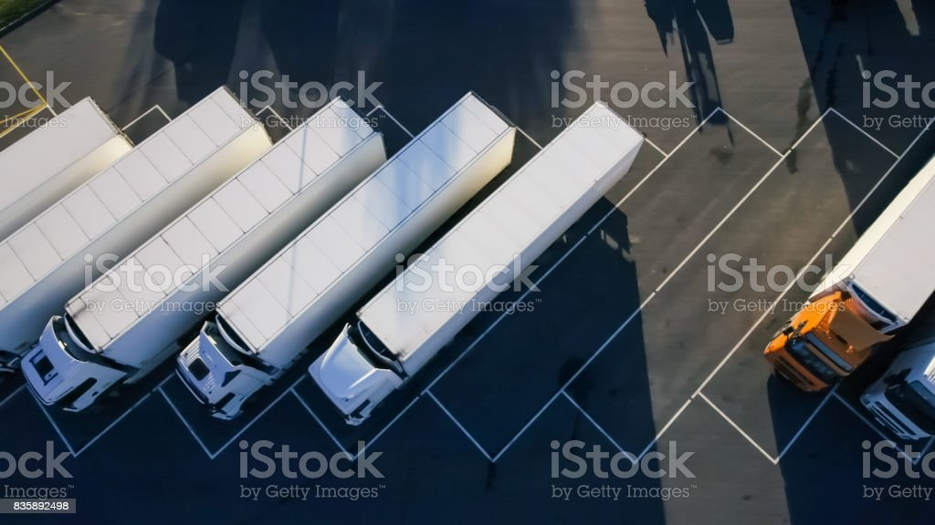 Aerial Top View of White Semi Truck with Cargo Trailer Parking with Other Vehicles on Special Parking Lot. Aerial Top View of White Semi Truck with Cargo Trailer Parking with Other Vehicles on Special Parking Lot. Above Stock Photo