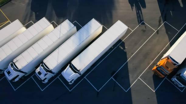 top luftaufnahme des weißen sattelschlepper mit cargo trailer mit anderen fahrzeugen auf speziellen parkplatz parken. - motionless in white stock-fotos und bilder
