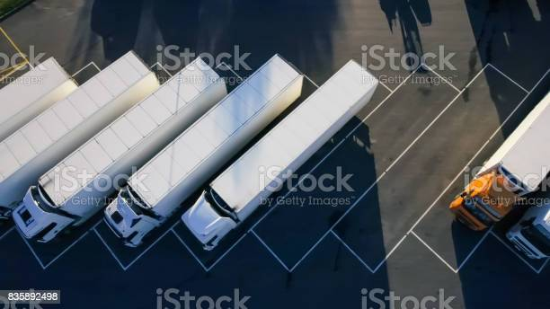 Aerial Top View Of White Semi Truck With Cargo Trailer Parking With Other Vehicles On Special Parking Lot Stock Photo - Download Image Now