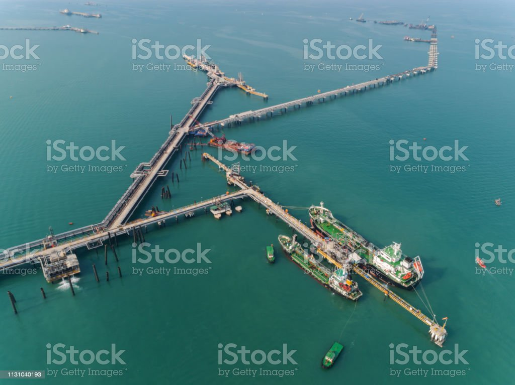 Aerial top view Oil ship tanker at refinery bridge on the sea loading...