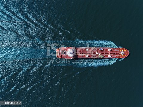 Aerial top view Oil tanker ship transportation oil from refinery with beautiful wave on the sea.