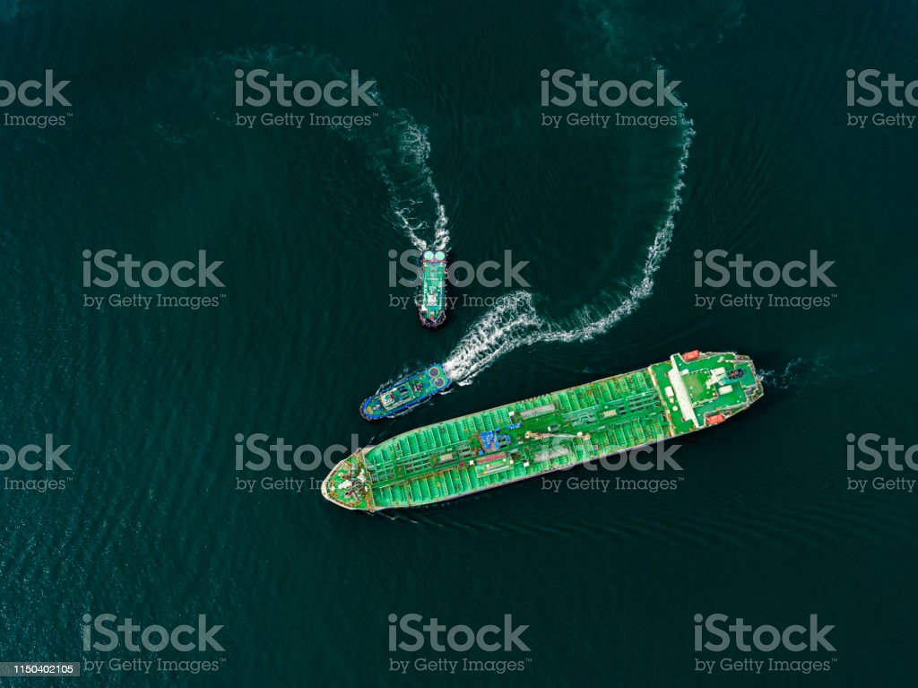 Aerial top view Tugboat drag Oil ship tanker on the sea going to...